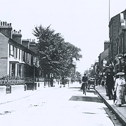 A lady walking down Mill Road in Cambridge wearing a large hat